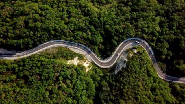 aerial top down view of mountain winding road with cars and trucks. - strada tortuosa video stock e b–roll