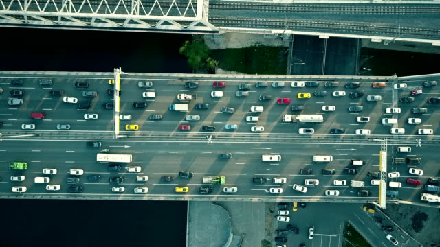 aerial top down view of traffic jam on a car bridge and moving train. fullhd video - ingorgo stradale video stock e b–roll