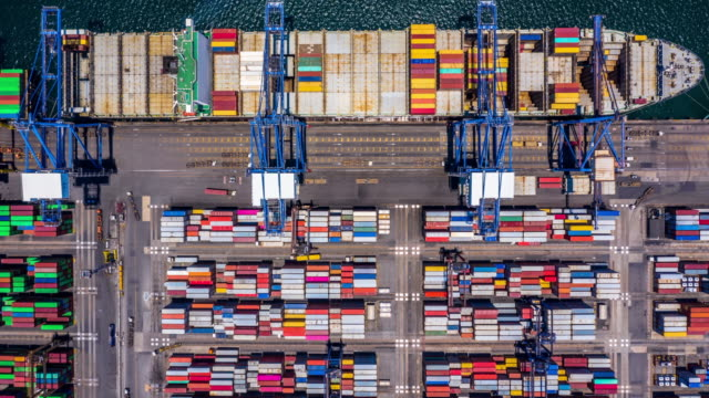 vídeos de stock e filmes b-roll de aerial top view 4k time lapse of container cargo ship in import export business logistic and transportation of international by container cargo ship in the open sea. - docas