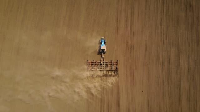 Flygvy blå traktor plöjning gården jord på fältet för sådd grödor video