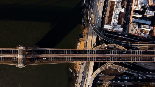 Aerial top view of Brooklyn bridge through the East river and road junction on Manhattan side in New York, America video