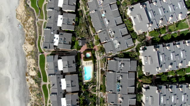 aerial top view of condo community next to the beach and sea in south california - osiedle mieszkaniowe filmów i materiałów b-roll