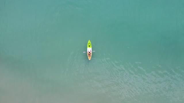 vidéos et rushes de vue aérienne de dessus du kayak autour de la mer avec l'eau bleue d'émeraude d'ombre dans la mer de la thaïlande - mer d'andaman