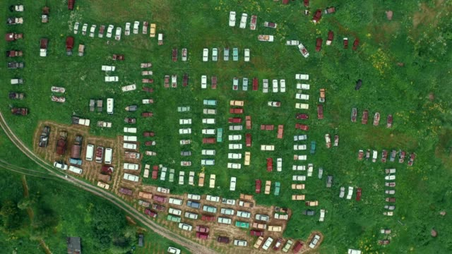 Aerial top view of many old retro rusty abandoned cars in green field, cemetery of vintage cars video