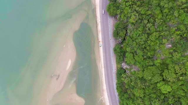 Aerial top view of scenic rural street between sea and mountain video