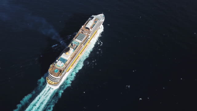 Aerial top view of stunning cruise ship at Black sea. Stock. Large cruise ship with people on the upper deck and a swimming pool with basketball field