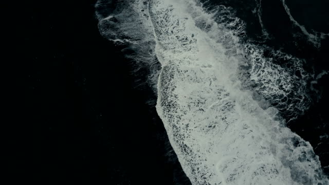 Aerial top view of the powerful wave with foam coming on the shore of black volcanic beach in Iceland
