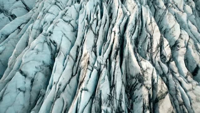 aerial top view of the ridges of white glacier with black ash. scenic iceberg in national park in iceland - trekking sul ghiaccio video stock e b–roll