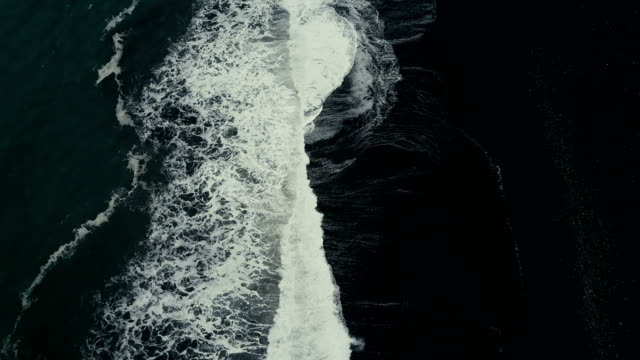 Aerial top view of the strong wave with foam coming to the shore of the black volcanic beach in Iceland video