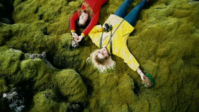 Aerial top view of the two happy woman lying on the soft moss in lava field in Iceland. Tourists resting on nature