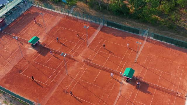 Luftaufnahme von nicht wiederzuerkennenden Tennisspielern, die an einem sonnigen Sommertag auf dem orangen Platz Tennis spielen – Video