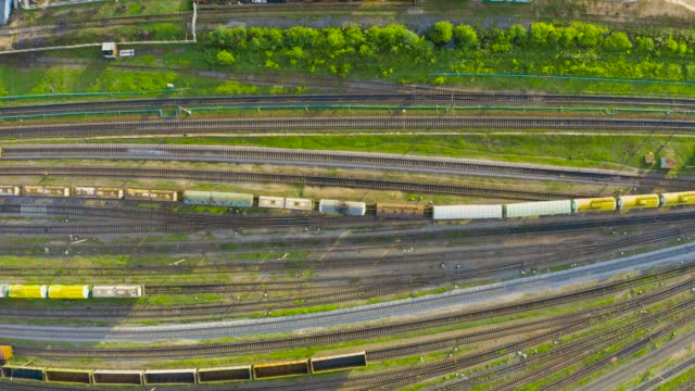 aerial top view of various railway carriage trains with goods on the railway station, freight train departure - parapetto barriera video stock e b–roll