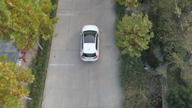 vídeos de stock e filmes b-roll de aerial top view of white car driving on small road in the valley and and countryside. china - carro na rua