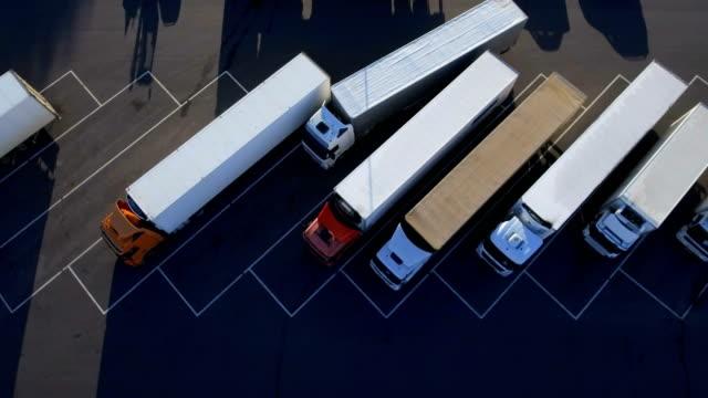stockvideo's en b-roll-footage met top luchtfoto van witte semi vrachtwagen met lading aanhangwagen met andere voertuigen op speciale parkeerplaats parkeren. - parkeren