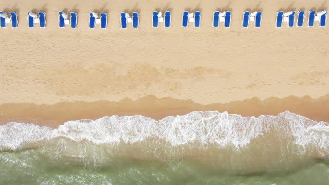 Aerial top view on the sandy beach. Umbrellas, sand, beach chairs and sea waves. Aerial top view on the sandy beach. Umbrellas, sand, beach chairs and sea waves. lounge chair stock videos & royalty-free footage
