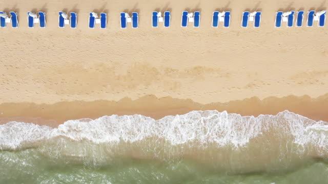 luftaufnahme am sandstrand. sonnenschirme, sand, strandkörbe und meereswellen. - sun chair stock-videos und b-roll-filmmaterial
