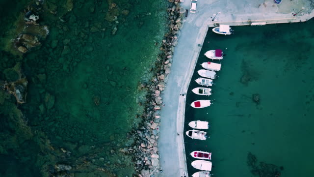 Aerial top view onto a pier with motorboats (drone footage) A small pier with speedboats / motorboats. A marina lot in Galatas, Crete, Greece near the beach. Yacht and sailboat at the quay. Aerial view by drone. Top view. greek islands stock videos & royalty-free footage