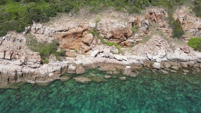 4K aerial top view, rock cliff coast and clear water sea