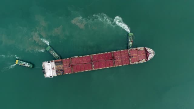 aerial top view three tug boat drag empty big container ship to seaport for loading container. logistics shipping, import export or transportation. - rimorchiatore video stock e b–roll