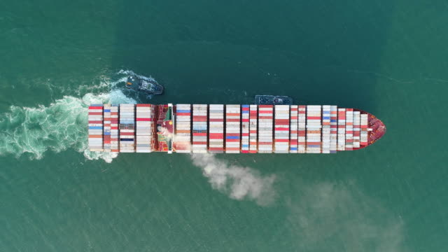 vídeos de stock e filmes b-roll de aerial top view tug boat drag container ship to sea port for shipping or transportation. - transatlântico