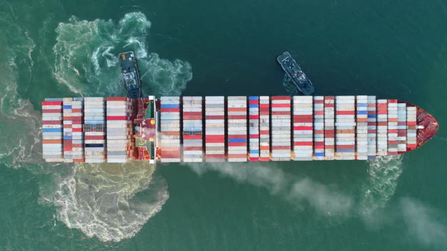aerial top view tug boat drag container ship to sea port for shipping or transportation. - rimorchiatore video stock e b–roll