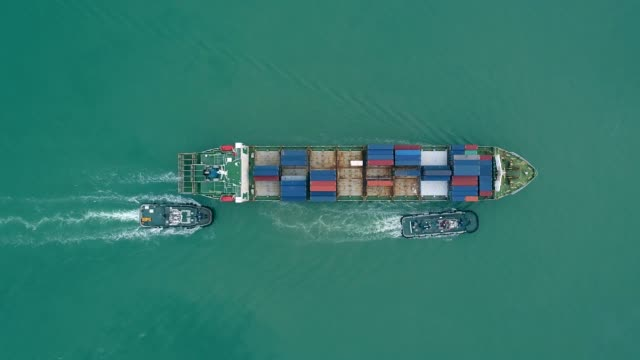 aerial top view tug boat drag container ship to seaport for logistics shipping, import export or transportation. - rimorchiatore video stock e b–roll