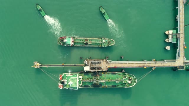 aerial top view tugboat drag oil tanker ship from refinery bridge for transportation on the sea. - rimorchiatore video stock e b–roll