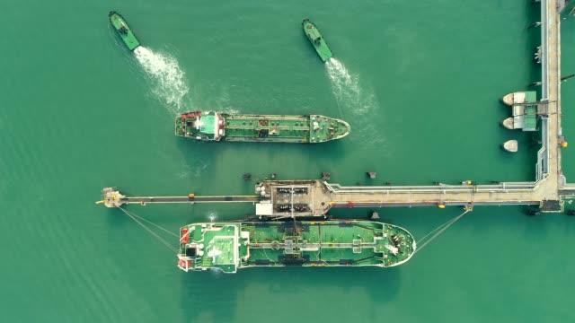 aerial top view tugboat drag oil tanker ship from refinery bridge for transportation on the sea. - gaz filmów i materiałów b-roll