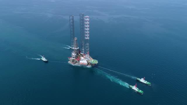 vídeos de stock, filmes e b-roll de o reboque superior aéreo arrasta o navio de petroleiro do petroleiro da ponte da refinaria para o transporte no mar - navio tanque embarcação industrial