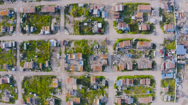 aerial top-down view high altitude of slum a heavily populated urban informal settlement characterized builders and wage workers substandard housing, squalor poor living conditions streets trailers - sezione superiore video stock e b–roll