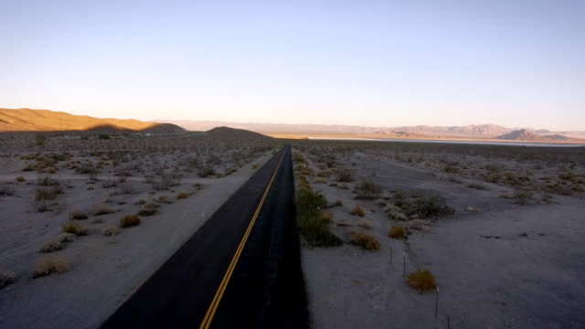 Aerial tracking shot along a single solitary road in the middle of nowhere. video