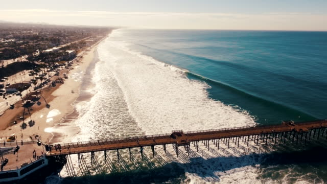 Aerial tracking shot of a beautiful sunrise sparkling off the ocean as the pier seems to go on forever into the blue abyss.
