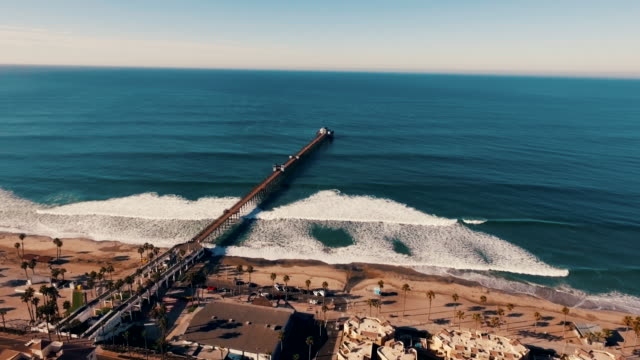 Aerial tracking shot of a beautiful sunrise sparkling off the ocean as the pier is revealed. video