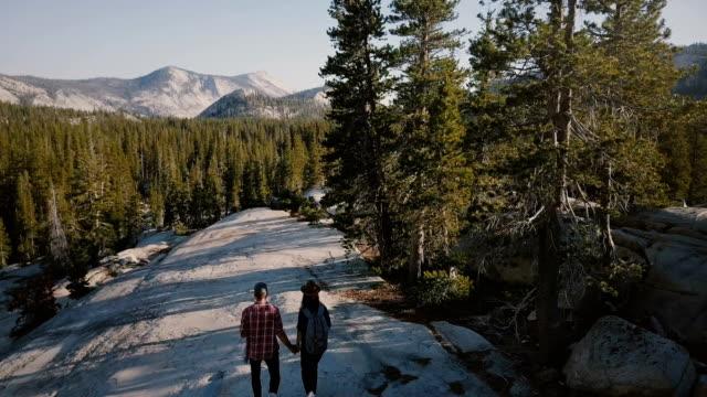 vidéos et rushes de travelling aérien de jeunes mariés randonnée ensemble sur roche blanche étonnante vers épique yosemite parc forestier skyline. - étendue sauvage scène non urbaine