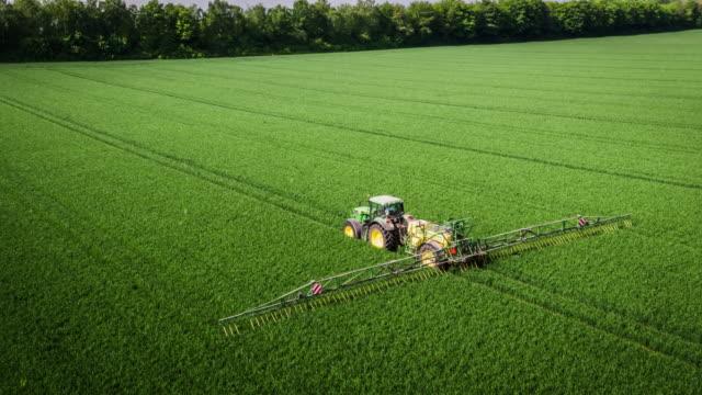 aerial: tractor applying liquid nitrogen fertilizer to corn field - fertilizzante video stock e b–roll