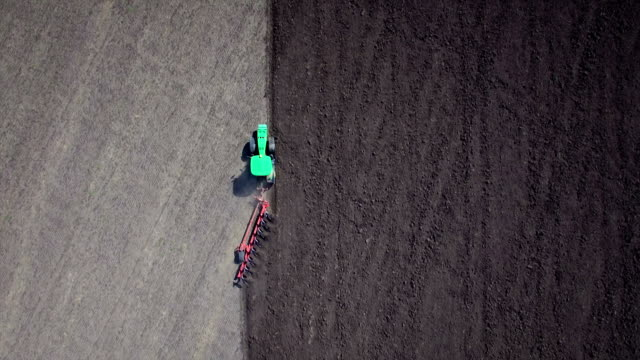 Aerial: Tractor plowing the soil. Top view. video