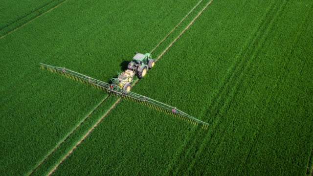 aerial: tractor spraying fertilizer on fields - trattore video stock e b–roll