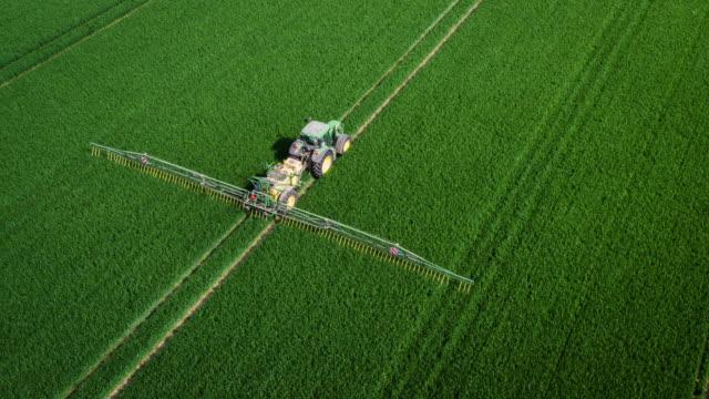 vidéos et rushes de antenne: tracteur, pulvérisation d'engrais dans les champs - herbicide