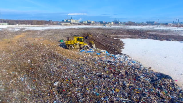 Aerial: tractor working at the garbage dump. Landfill, garbage dump, trash dump from above. video