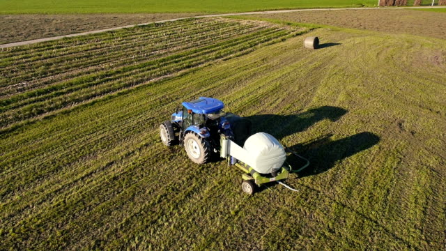 Aerial: Tractor wrapping and releasing bale of hay video
