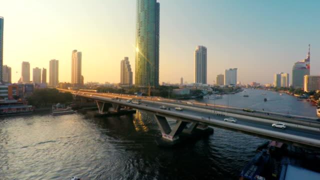veduta aerea, il traffico su bridge al tramonto - fiume chao phraya video stock e b–roll