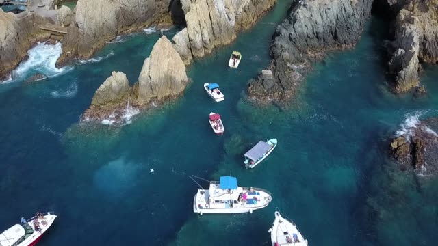 aerial traveling out over some yachts in the quebrada in acapulco, mexico - guerrero video stock e b–roll
