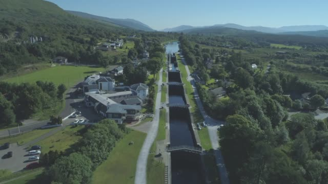aerial travelling down the neptune's staircase series of locks on the caledonian canal in banavie, fort william, scotland - fort william video stock e b–roll