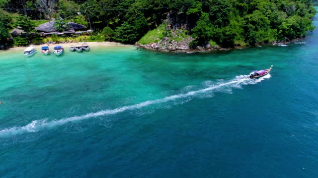 aerial: two boats leave from the phi phi don beach. - phuket video stock e b–roll