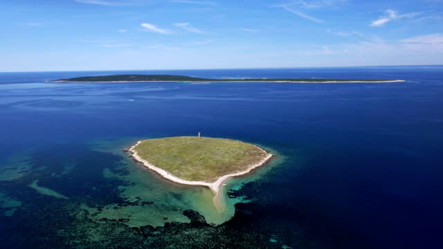 Aerial: two small Croatian islands with green land and nice blue water around video