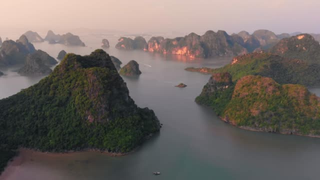aerial: unique flying over ha long bay and cat ba island at sunset, famous tourism destination in vietnam. scenic sky with clouds, limestone rock peaks in the sea at the horizon. - arcipelago video stock e b–roll