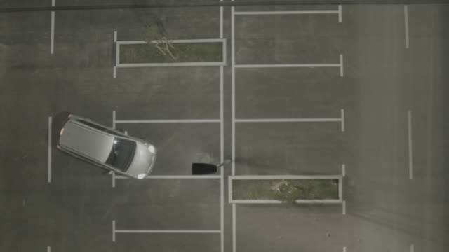 4K Aerial: Vertical Lift Above Upcoming Car on Empty Park Lot video