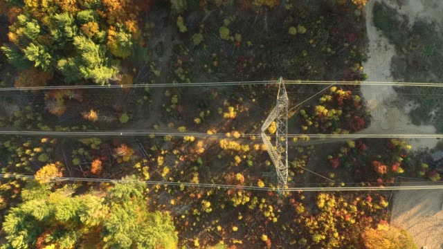 Aerial vertical overhead shot of power pylon carrying hydro electricity This clip is part of a collection of stunning autumn fall foliage footage in 4K Ultra High Definition - Dark but pure waters of a river flowing and guided thru heavy epic bedrock high voltage sign stock videos & royalty-free footage