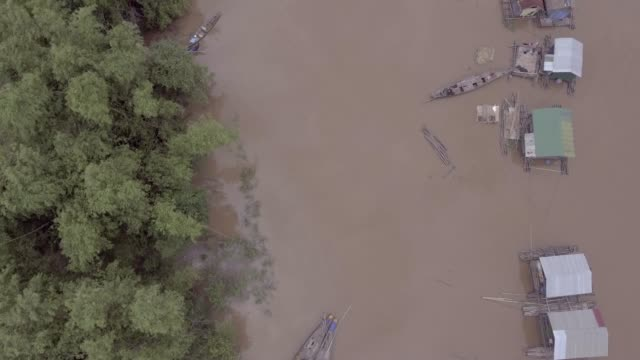 aerial vertical shot looking down along over floating houses on the riverbank flooded by torrential rains - monsone video stock e b–roll