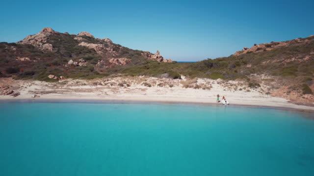 aerial video of a paradisiac beach on the island of mortorio in sardinia, incredible island of the emerald coast in italy - sardegna video stock e b–roll